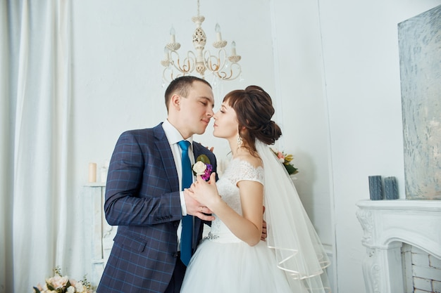 신부와 신랑 결혼식 옷 포옹 집에서. 결혼식 후 사랑에 몇