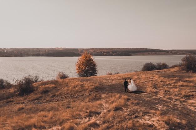 ウェディングドレスを着た新郎新婦が川の近くの秋の赤いフィールドに沿って歩く