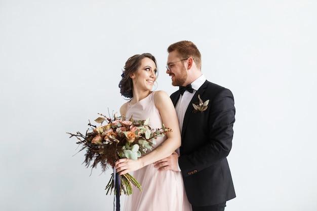 花嫁、新郎新婦、白い壁の背景に隔離された。