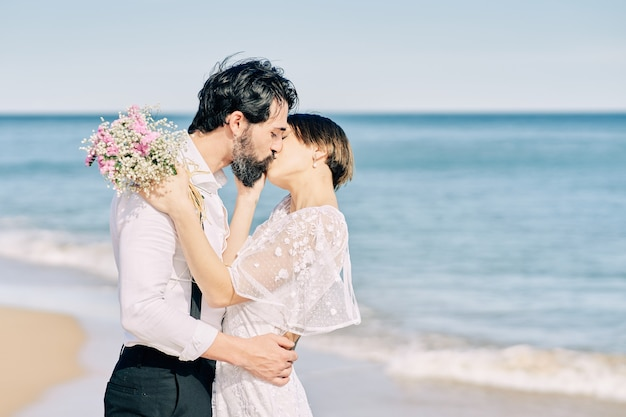 행복하게 그들의 결혼식을 축하하는 해변에서 키스하는 신랑과 신부