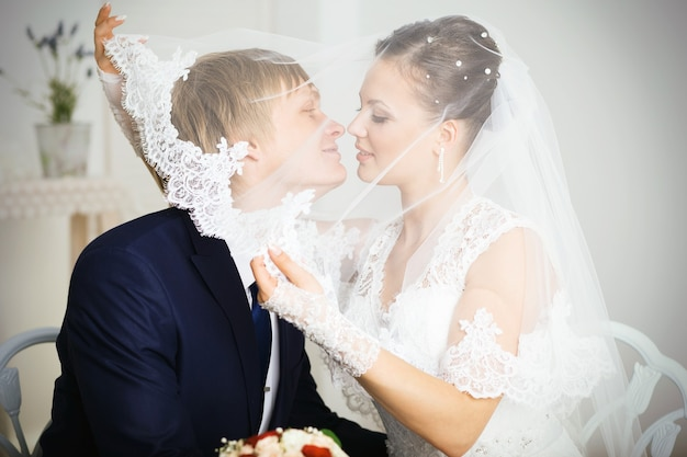 花の花束を手に持ってベールの下でキスする新郎新婦。