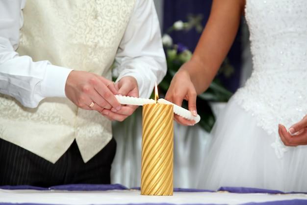 新郎新婦が式典で結婚式のキャンドルを灯します