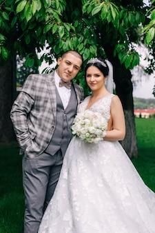 公園でカメラを見ている新郎新婦。白い結婚式の花束を保持している花嫁。