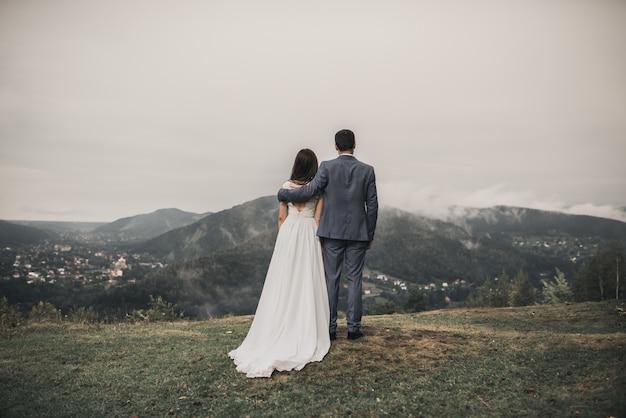 Жених и невеста, глядя на лес в горах в тумане
