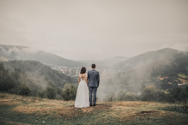 霧の中で山の森を見ている新郎新婦