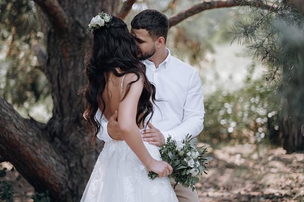 신부와 신랑. 첫 번째 가족 결혼식 사진 촬영을 위해 포즈를 취하는 사랑에 빠진 고급스러운 젊은 부부