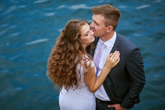 結婚式の日に湖の近くの新郎新婦。
