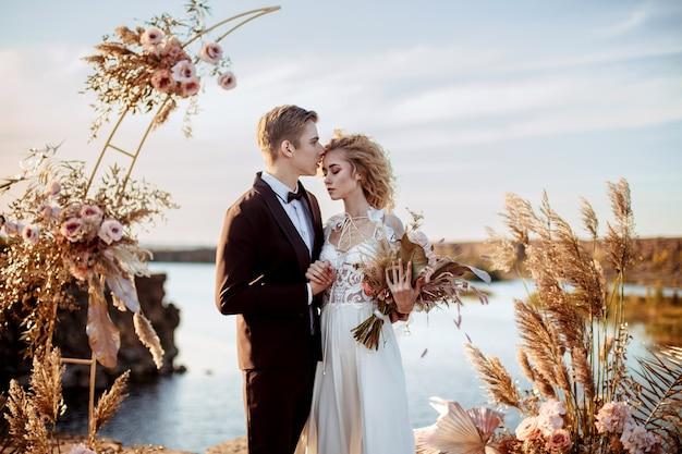 Жених и невеста возле свадебного украшения на церемонии на скале у воды на закате