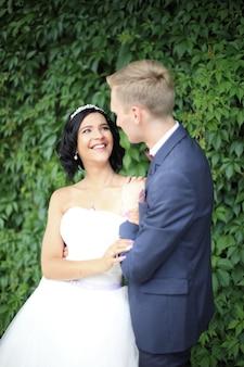 Жених и невеста на фоне зеленых листьев