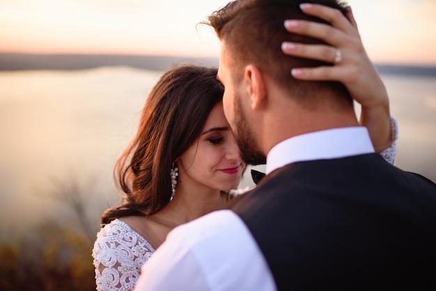 Жених и невеста на фоне озера