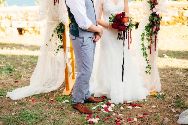 結婚式のアーチの下の芝生の上の新郎新婦