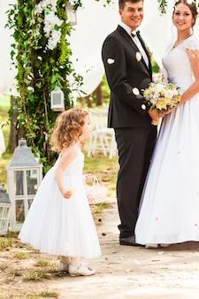 Жених и невеста на свадебной церемонии. очаровательная девушка осыпала молодоженов летающими лепестками роз