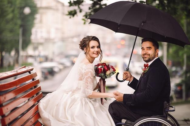 車椅子の花嫁と新郎は公園のベンチでキスをして座っている