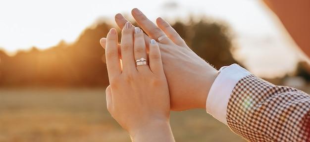 결혼식 날 신랑과 신부가 해질녘에 포옹하고 반지를 봅니다.