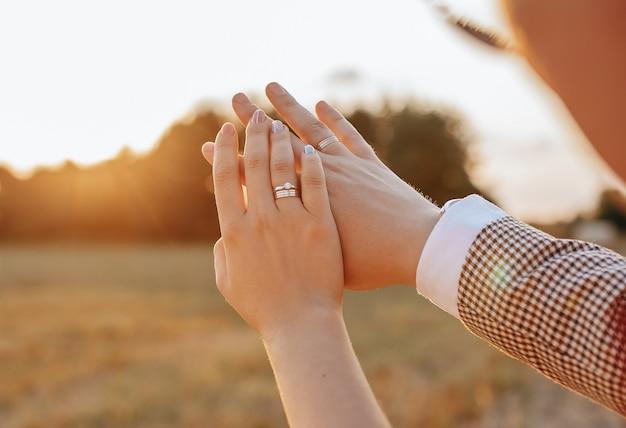Жених и невеста в день свадьбы обнимаются и смотрят кольца на закате