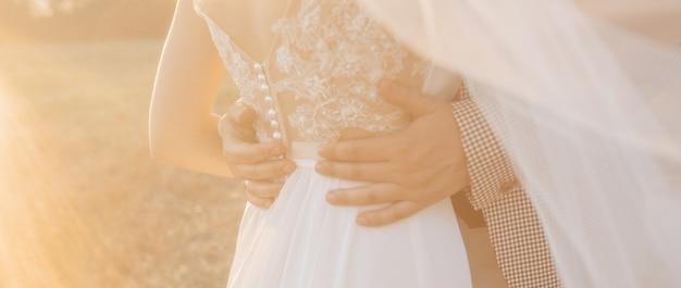 Жених и невеста в день свадьбы обнимаются и показывают любовь на закате размытие фона