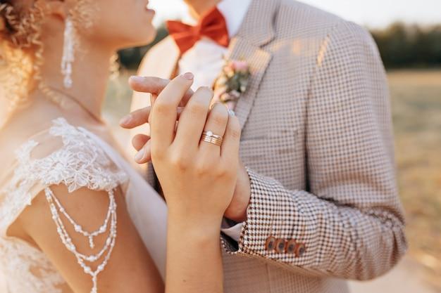 Жених и невеста в день свадьбы обнимаются и показывают любовь на закате