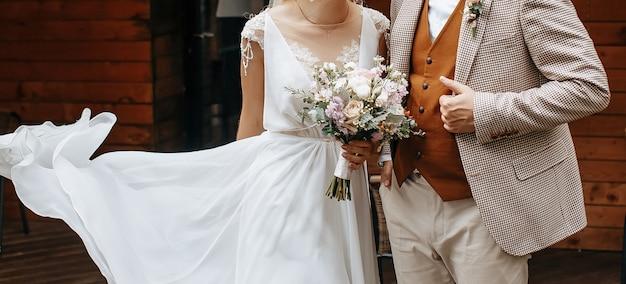 結婚式の日の新郎新婦は、バラの花のウェディングブーケで抱きしめ、愛を示します