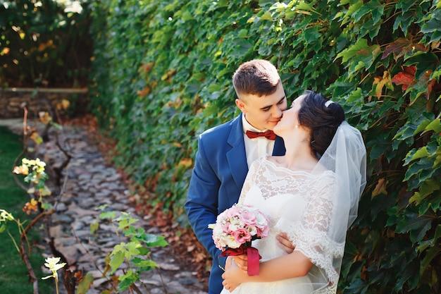 Жених и невеста позирует в парке