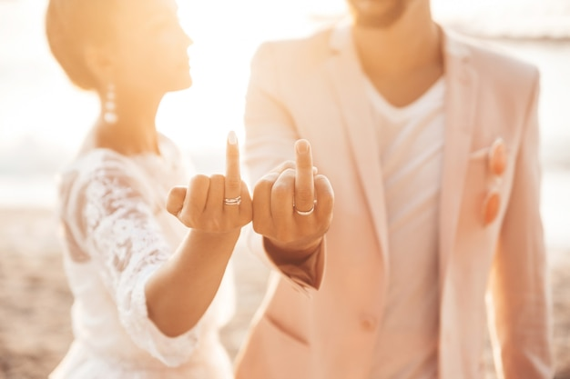 Жених и невеста позируют на пляже на закате