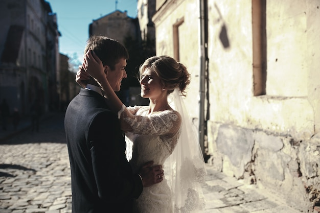 Жених и невеста позируют на улицах старого города