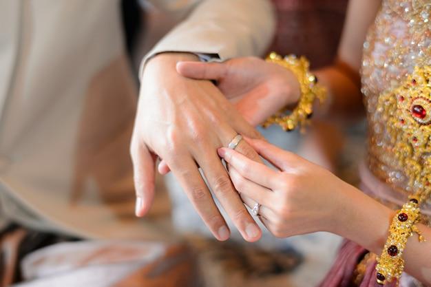 新郎新婦がリングタイの結婚式の婚約を置く