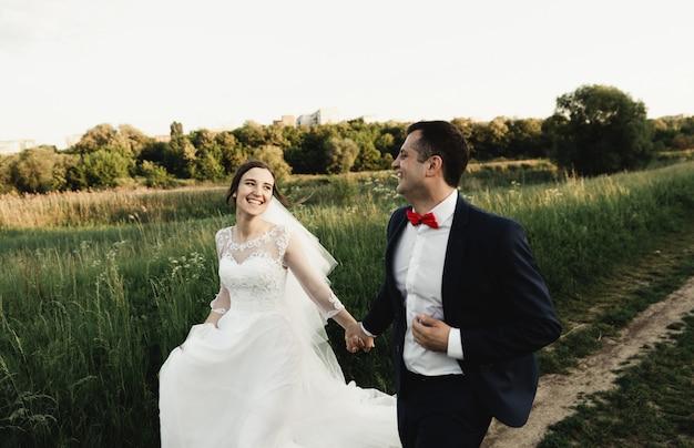 신부와 신랑 일몰 결혼식 날에 들판을 가로 질러 실행