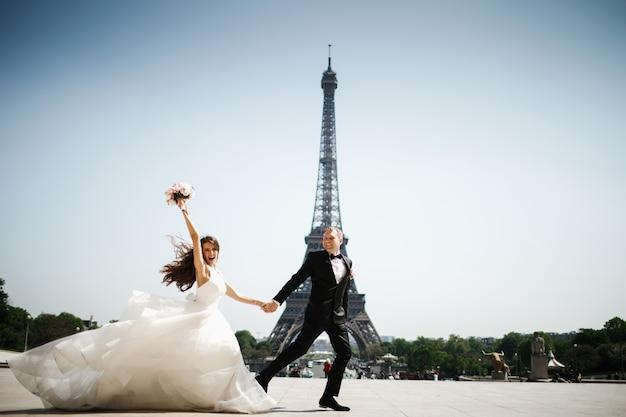 パリのエッフェル塔の前で花嫁と新郎が走る