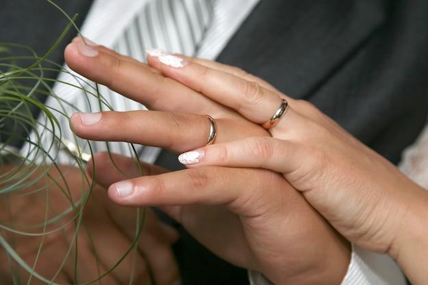 신부와 신랑은 결혼 반지를 끼고 손을 보여줍니다. 두 영혼의 통일
