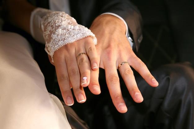 신부와 신랑은 결혼 반지를 끼고 손을 보여줍니다.