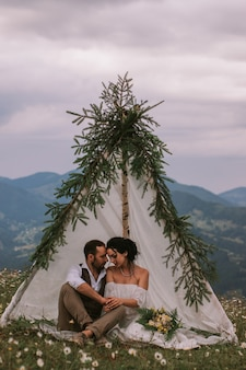 結婚式の小屋に座っている新郎新婦