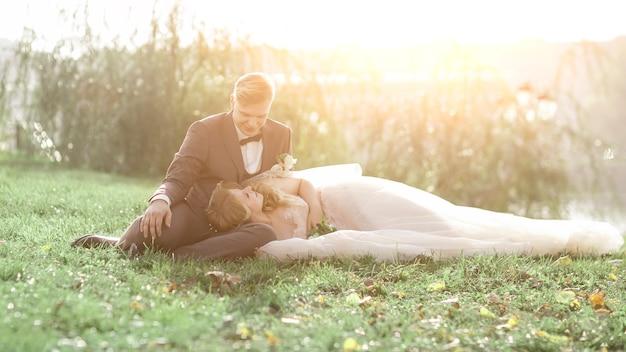 Жених и невеста сидят на лужайке в городском парке. фото с копией пространства