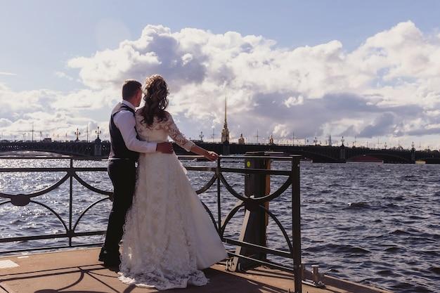 新郎新婦は川と大聖堂の背景に抱きしめて立っています。晴れた結婚式の日にウェディングドレスを着た新婚夫婦。素晴らしい景色の中で自然のカップル。一緒に幸せな恋の新婚夫婦