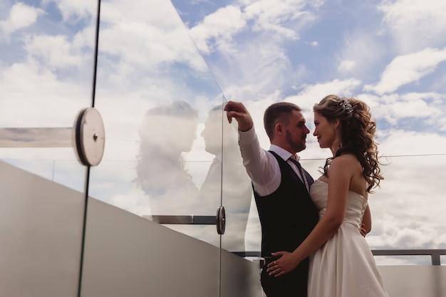 花嫁と花婿は雲と青空の背景に抱きしめて立っています。晴れた結婚式の日にウェディングドレスを着た新婚夫婦。素晴らしい景色の中で自然のカップル。一緒に幸せな恋の新婚夫婦