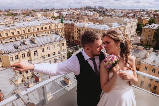 花嫁と花婿は、旧市街のパノラマの景色を眺めながら屋根に抱きしめています。晴れた結婚式の日にウェディングドレスを着た新婚夫婦。素晴らしい景色を望む屋根の上のカップル。街を背景に恋する新婚夫婦