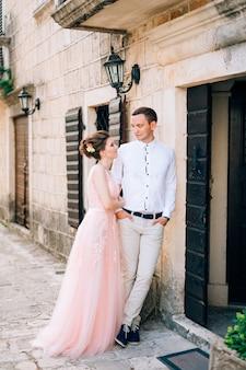 Жених и невеста обнимаются у старинного дома.