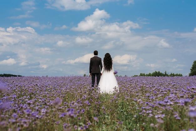 Жених и невеста стоят в поле цветов летом в день свадьбы