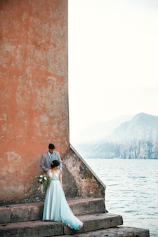 Bride and groom stand together on the shore before the sea