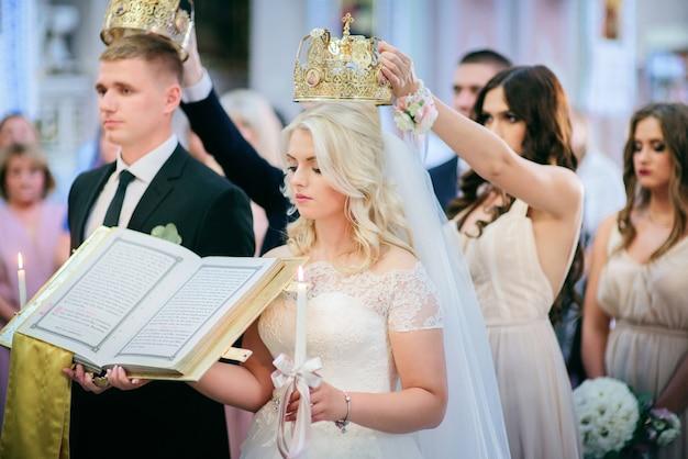 Жених и невеста стоят с коронами перед священником