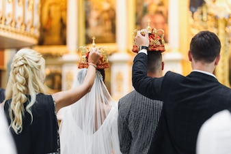 Bride and groom stand with crowns during the ceremony in church