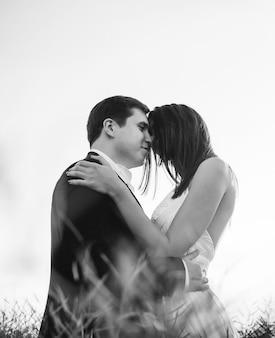 «жених и невеста, стоящих в обнимании в поле»