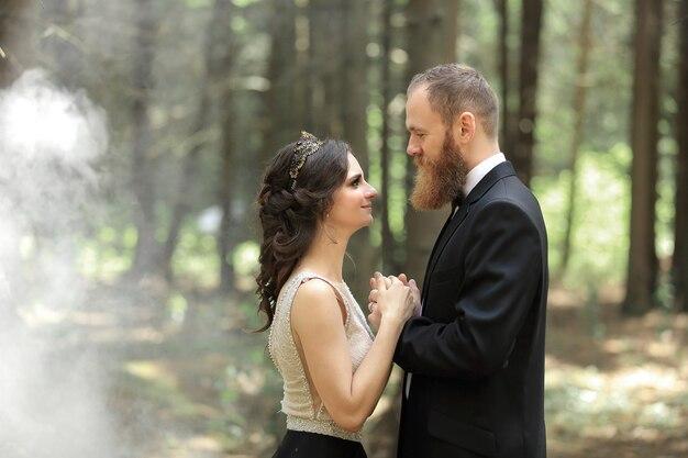 Жених и невеста стоят в лесу. фото с эффектом облаков