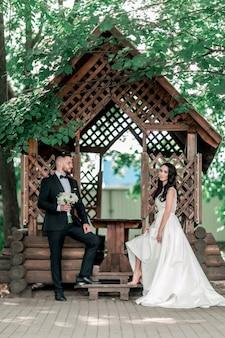 Жених и невеста, стоя возле беседки в парке