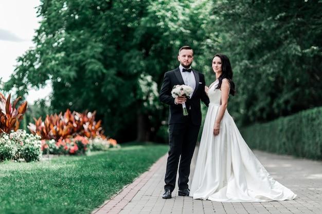 Жених и невеста, стоя на дорожке в городском парке