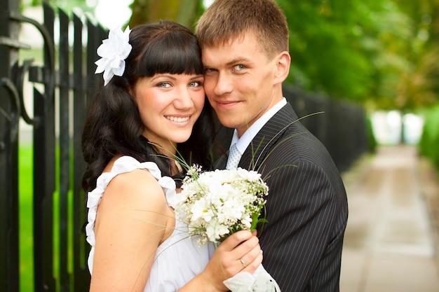 Жених и невеста, стоя вместе в парке