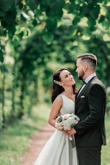 Жених и невеста стоят под свадебной аркой