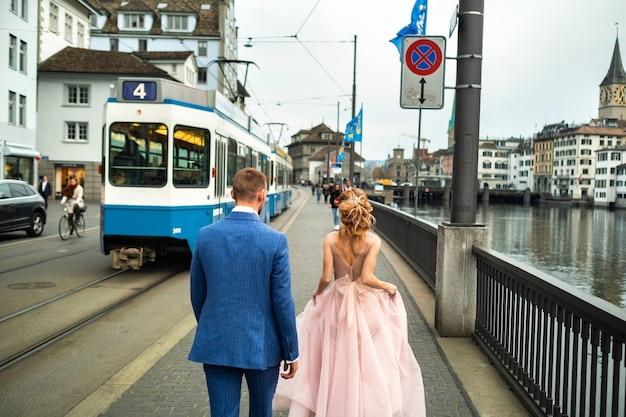 신부와 신랑은 스위스 취리히 도심의 리 마트 강 제방을 따라 걸어갑니다.