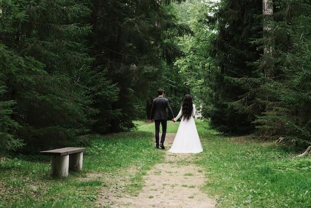 Жених и невеста гуляют по аллее парка летом в день свадьбы