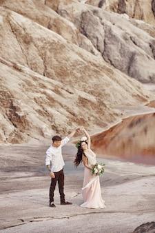 新郎新婦は赤い山々、素晴らしい景色を歩きます。手をつないで恋にカップル。屋外で秋の結婚式