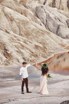 新郎新婦が赤い山々を散歩する素晴らしい景色。手をつないで恋にカップル。屋外で秋の結婚式